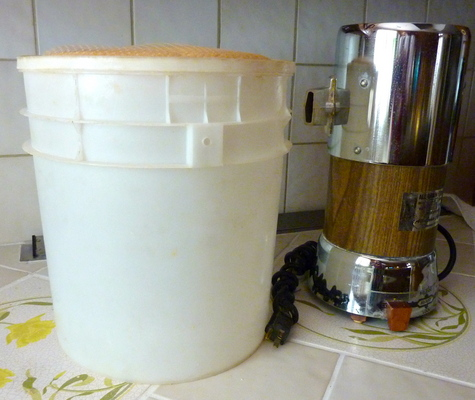 All grain flour mill with plastic container to catch flour.