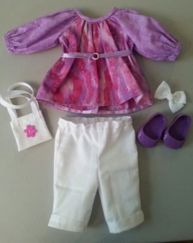 Pink and purple tunic with attached ribbon belt, white capries, purple shoes, hair bow, purse with reversable sides.