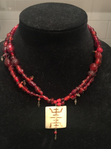 Burgundy beaded necklace with cream pendant